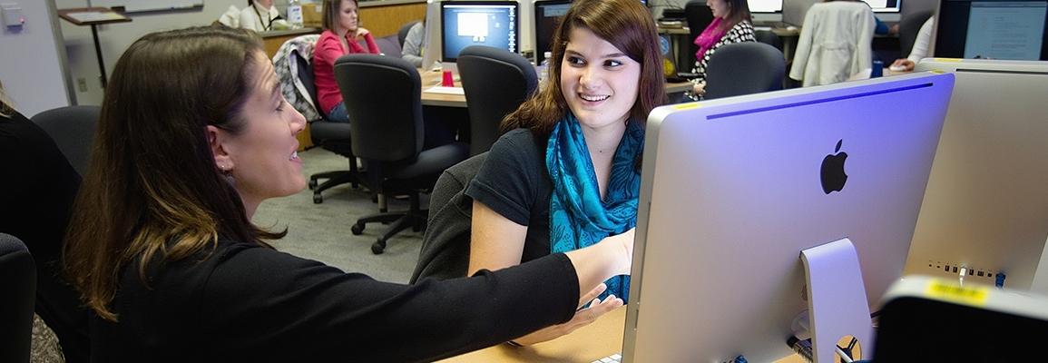 Instructor helping student working on desktop computer