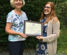Jenny Darcy accepts an award from PEO International Chapter president, Jan Noffsinger.