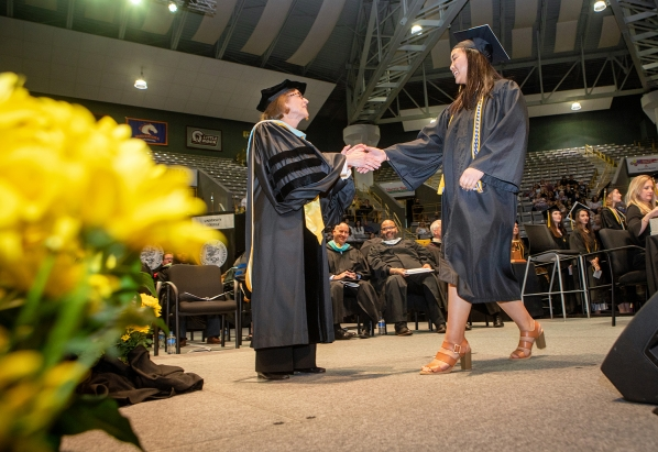 Dean Spooner shakes students hand at commencement.