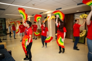 High school students learning Chinese dance movements during a cultural workshop.