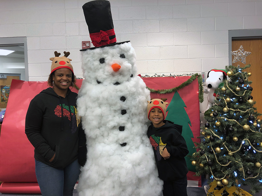 Chantae Reynolds, ESL teacher and parent at the Academy, and her son, Jameson Kankula, pose for picture with our very own Frosty (aka Coach Phelps).