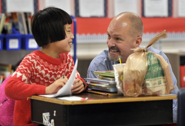 Eric Groce, professor of education at Appalachian State, talks with Middle Fork Elementary School third-grader Joanna Meng.