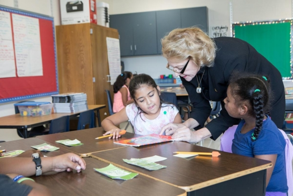 At the Appalachian State University Academy at Middle Fork, Appalachian Chancellor Sheri Everts prepares to read a story with students in the third grade classroom of teacher Heather Wham. Students photographed are: Clarise Serrano-Hernandez and Yarel Candela-Lucero. Photo by Marie Freeman