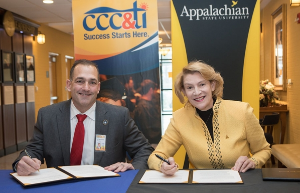 Caldwell Community College and Technical Institute President Dr. Mark Poarch, left, and Appalachian State University Chancellor Dr. Sheri Everts sign the Aspire Appalachian Co-Admission Program agreement on Wednesday, Dec. 12, in the B.B. Dougherty Administration Building on Appalachian's campus in Boone. Photo by Marie Freeman