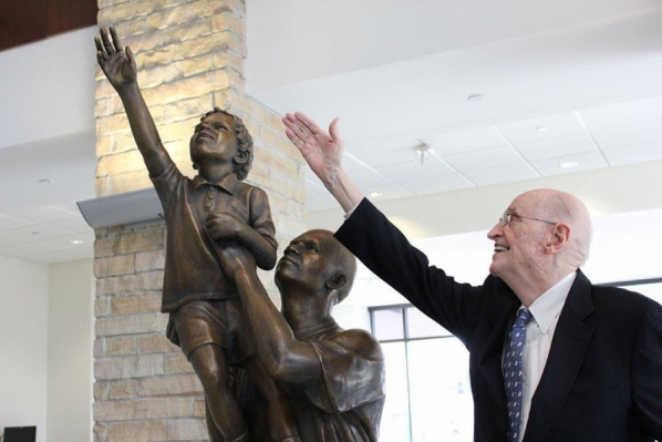 "Irwin ""Ike"" Belk mimics the gesture of the bronze boy in ""Just Reach a Little Higher,"" a sculpture he commissioned for the Reich College of Education in 2012."