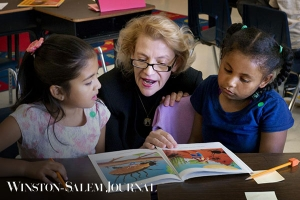 Chancellor Sheri Everts reads to Academy third-graders Larise Serrano Hernandez (left) and Yarel Candela-Lucero on Thursday.