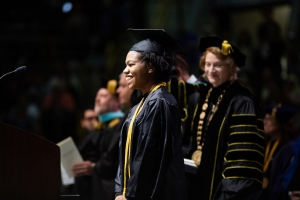 Graduating senior Maya Brown-Hughston approaches the podium as Appalachian State University Chancellor Sheri Everts looks on. Photo by Chase Reynolds